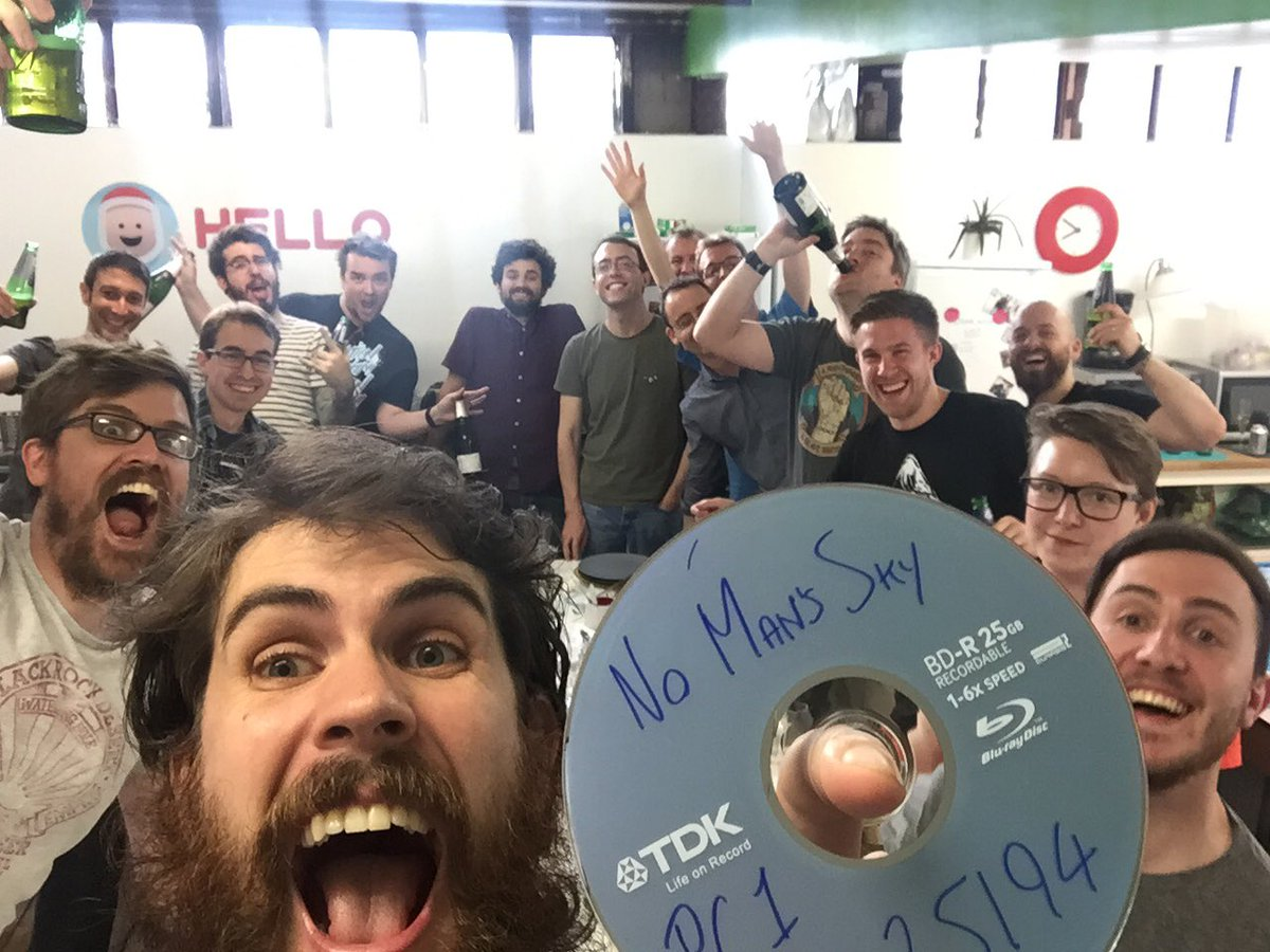 Sean Murray and Hello Games staff hold No Man's Sky DVD